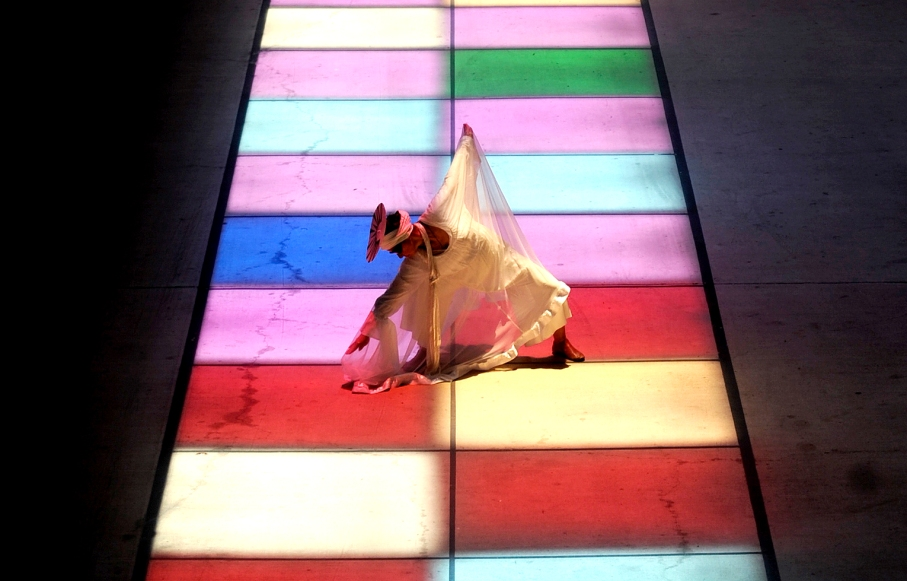 Catherine Cisneros performs a dance as a celebration of the Summer Solstice in the lighted squares created by the artwork